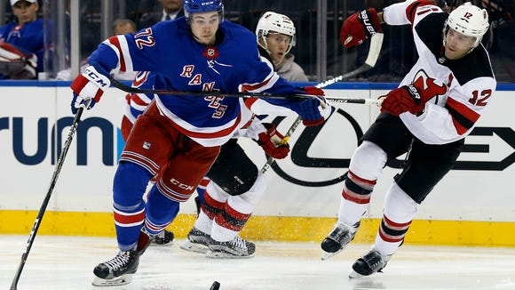 New York Rangers center Filip Chytil (72) vies for the puck with New Jersey Devils defenseman Ben Lovejoy (12) during the second period of an NHL preseason hockey game Wednesday, Sept. 20, 2017, in New York. (AP Photo/Adam Hunger)