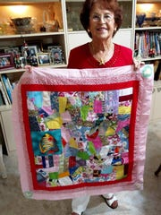 Club member Marie Senechal displays one of the quilts she donated to the Shelter for Abused Women and Children.