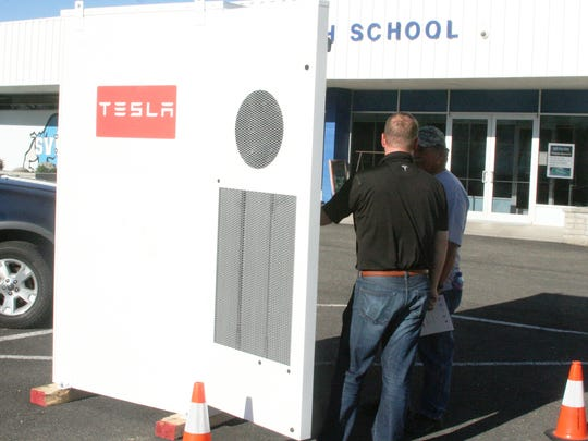 Kevin Kassekert (right), a director of infrastructure development for Tesla based in Sparks, shows the inside of a new Tesla commercial storage battery to Smith Valley resident John Abrott Wednesday evening during a NV Energy open house for Smith Valley customers, where one option for electrical improvements in that area is to use about 50 of these storage batteries.