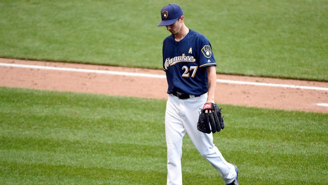 Brewers pitcher Zach Davies walks back to the dugout after a pitching change in the seventh inning against the Chicago Cubs on Saturday at Miller Park.