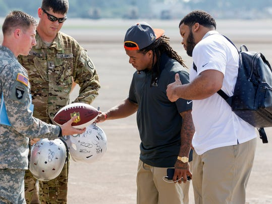 Atlanta Falcons Devonta Freeman, second from right, and Los Angeles Rams Aaron Donald, right, sign autographs for United States Army personnel before the NFL Pro Bowl Football Draft at the Wheeler Army Airfield, Wednesday, Jan. 27, 2016, in Wahiawa, Hawaii. (AP Photo/Eugene Tanner)