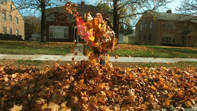 In this Nov. 10, 1997 photo, Marilyn Martz clears what looks like the last fall of maple leaves from the front of her walk on N. Port Washington Road in Glendale.