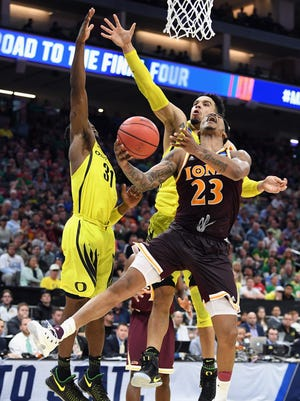 Jordan Washington #23 of the Iona Gaels drives to the basket against Dylan Ennis #31 and Dillon Brooks #24 of the Oregon Ducks in the second half during the first round of the 2017 NCAA Men's Basketball Tournament at Golden 1 Center on March 17, 2017 in Sacramento, California.