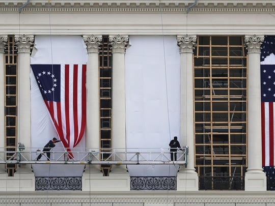 WASHINGTON, DC - JANUARY 13:  Workers hang an early version of the American flag on the U.S. Capitol to be used as part of the backdrop to the presidential inauguration for President elect Donald Trump as he prepares to take the reins of power next week on January 13, 2017 in Washington, DC.  The inauguration will take place on January 20th when President Barack Obama ends his 8 year run as Americas president.
