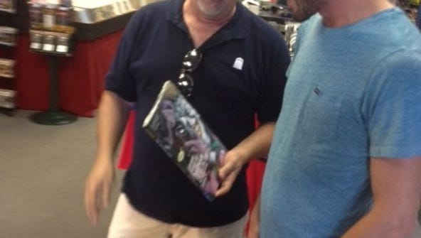 Comic book store owner Chuck Cagle shows customer Chris