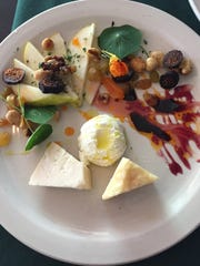 A plate of cheese and fruit with honey walnuts at Devotay