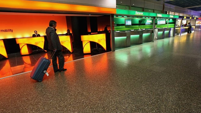 A traveller walks in front of car rental counters at Frankfurt airport