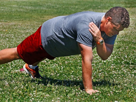 Jason Neubauer, shows the shoulder tap as a modification for the walking plank exercise.