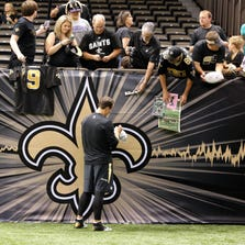 Aug 28, 2014; New Orleans, LA, USA; New Orleans Saints quarterback Drew Brees (9) autographs items for fans before their game against the Baltimore Ravens at the Mercedes-Benz Superdome.