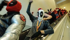 A long line of Deadpool cosplayers cheer in unison