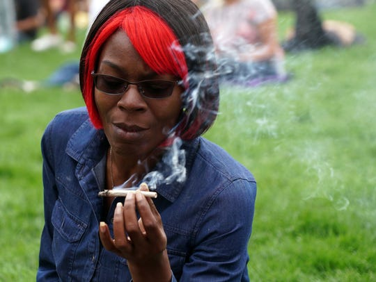 In this file photo, an attendee at the 2017 420 rally in Denver inspects her joint while smoking.
