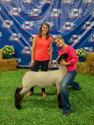 Riley Leonard (right) sold a lamb at the 2019 Ionia Free Fair Youth Livestock Auction. It was purchased by Bridget Badder from Harvey's.