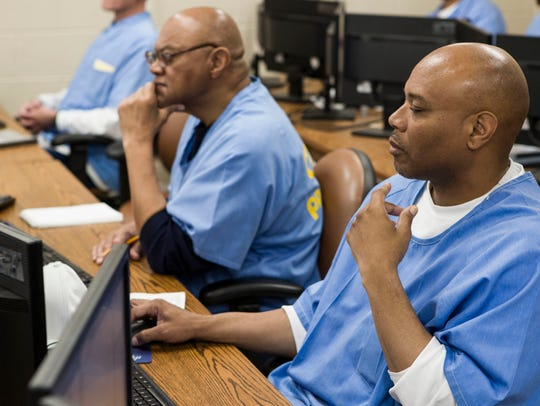 San Quentin inmate Nelson Butler, right, takes a coding