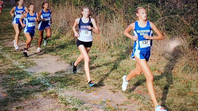 Washburn Rural's Madeline Carter (137) and Seaman's Bethany Druse (33) lead the pack in Saturday's city girls cross country meet.