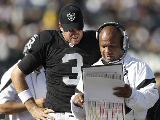 Carson Palmer talks with then-head coach Hue Jackson after the Raiders acquired the quarterback in 2011.