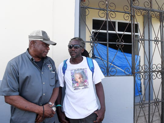 Carl Francis, right, talks about his 2-year-old son, Carl, who lost his life in Hurricane Irma on the island of Barbuda, with Bishop Nigel Henry, November 7, 2017.