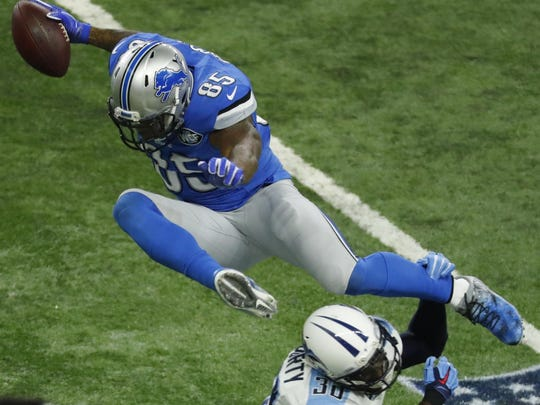 Lions tight end Eric Ebron leaps over Titans cornerback Jason McCourty (30) after a reception during the first half Sunday.