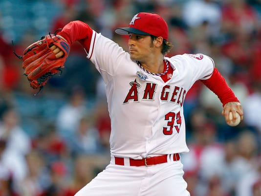 Los Angeles Angels starting pitcher C.J. Wilson throws against the Houston Astros in the first inning of a baseball game on Friday, July 4, 2014, in Anaheim, Calif. (AP Photo/Alex Gallardo)