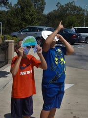 Caelan Reynolds (left) and Nathan Yarborough watch the solar eclipse Monday at the Donald W. Reynolds Library in Mountain Home.