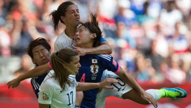 United States' Carli Lloyd, top, collides with Japan's Saki Kumagai (4) during the first half of the FIFA Women's World Cup soccer championship in Vancouver, British Columbia, Canada, on Sunday, July 5, 2015.