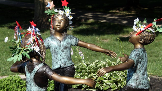 The children's statue in Clinton's Central Park has been decorated by community members for different occasions. For the Fourth of July, they sported red, white and blue.