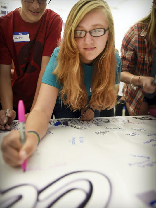 Soon-to-be Cedar Crest High School student Meghan Yingst signs a pledge to graduate during a freshman orientation last week.