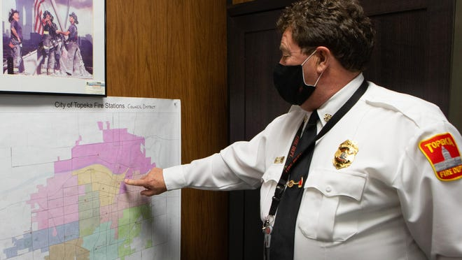 Topeka Fire Department Chief Craig Duke points out the number of fire stations located on a district map in his office, stating the reason some stations were placed where they are is correlated with horse-drawn firetrucks' inability to travel longer distances.