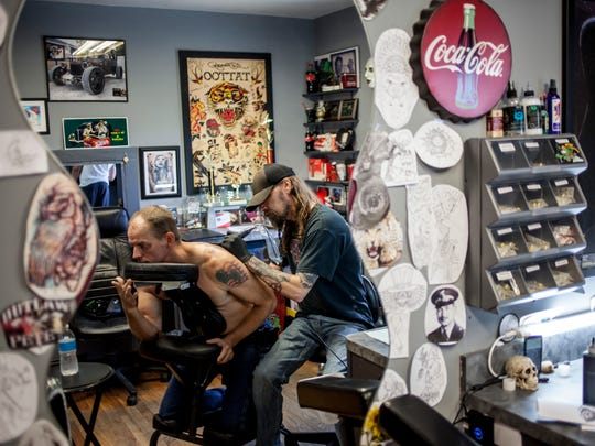 Jon Reno works on a tattoo with Michael Spangler, of Redford, Friday, June 30, 2017 at DaVinci Tattoo in Port Huron.