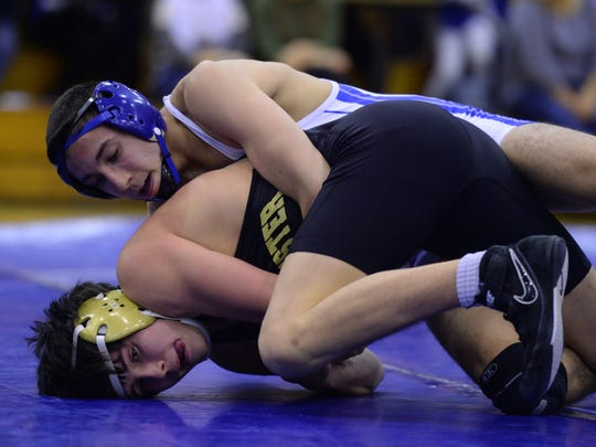 Centerville's Javon Phillips, top, wrestles Winchester's