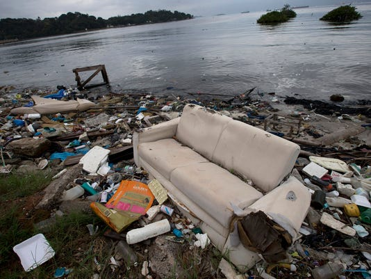 FILE - In this June 1, 2015 file photo, a discarded sofa litters the shore of Guanabara Bay in Rio de Janeiro, Brazil. With thousands of liters of raw human sewage pouring into the ocean every second from Rio, August's Olympic Games have thrust into the global spotlight Rio's spectacular failure to clean up its waterways and world famous beaches. (AP Photo/Silvia Izquierdo, File)
