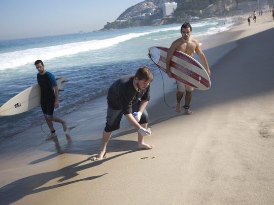 In this July 11, 2016 photo, doctoral candidate Rodrigo Staggemeier collects samples of sand from Ipanema beach, for a study commissioned by The Associated Press, in Rio de Janeiro, Brazil.
