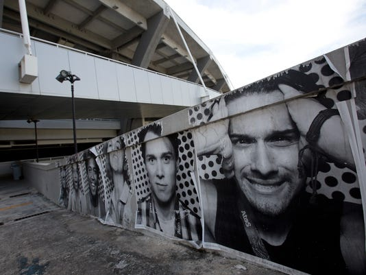 In this Feb. 2, 2017 photo, photos of Olympic volunteers hang at Maracana stadium in Rio de Janeiro, Brazil. Rio de Janeiro pulled off last year's Olympics, keeping crime at bay and fending off dire forecasts linked to corruption, environmental degradation and budget cuts as Brazil plunged into its deepest recession in memory. Six months after South America's first games, the flood gates have burst open. (AP Photo/Silvia Izquierdo)