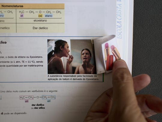 This photo shows a page in a schoolbook with a printed picture of a woman applying lipstick covered with another image in Belo Horizonte, Brazil. This and other schoolbooks used by members of the Word of Faith Fellowship church in Brazil show heavy redactions. Instead of human sexuality, for example, the life cycle is taught via plant reproduction.