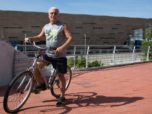 """In this July 16, 2017 photo, Salvador Gaeta poses for a photo at the Olympic Park, in Rio de Janeiro, Brazil. The park is open to the public on weekends but offers few amenities: no restaurants, no shade, and nothing much to do except gawk at deserted arenas. """"It's the only medal that really mattered,""""  """"Every Brazilian will remember it,""""  Gaeta said. When soccer star Neymar kissed the ball, delivered a gold medal, and then wept with other Brazilians, during the Rio de Janeiro Olympics. (AP Photo/Renata Brito)"""