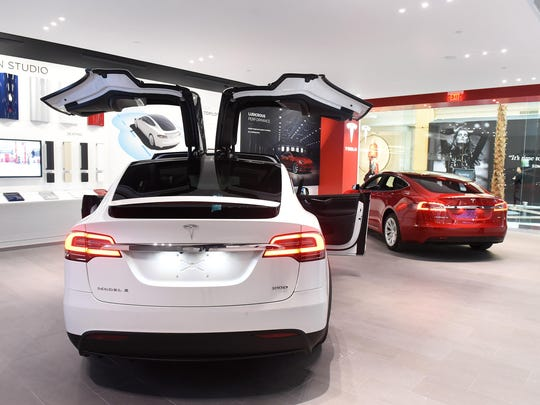 The 2,200-square foot gallery features a Model S, right, and a Model X — an $80,000 SUV that shares the $70,000 sedan's platform.