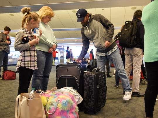 Chris Amerson, right, brings over a bag with his daughter,