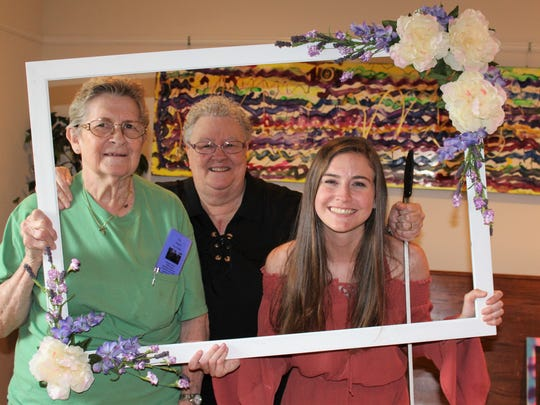 Sissy Heathccott, left, and Brylee Grubb Erwin, right, frame retiring pastor Margaret Warn-Walker at a reception June 9 at Metropolitan Exodus Community Church. Picture frames of different sizes were provided for photo ops, like this.