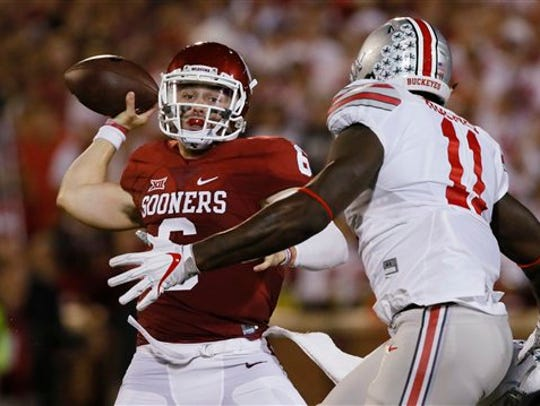 Oklahoma quarterback Baker Mayfield, left, throws under