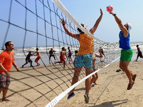 Beach-goers play a game of volleyball during spring