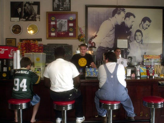 "FILE - This June 23, 2004 file photo shows the cafe counter at Sun Studio in Memphis, Tenn., with a photo of the ""Million Dollar Quartet"" on the wall. The famous 1956 image shows Elvis Presley, who got his start at Sun Studio, seated with Jerry Lee Lewis, Carl Perkins and Johnny Cash standing. Lively guided tours of Sun Studio walk visitors through its hit parade with music clips, lively exhibits and engaging anecdotes."