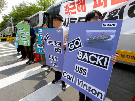 "South Korean protesters stage a rally against U.S. deployment of the USS Carl Vinson aircraft carrier and its battle group to the Korean Peninsula, in front of the Defense Ministry in Seoul, South Korea, Tuesday, April 25, 2017. North Korea marks the founding anniversary of its military on Tuesday, and South Korea and its allies are bracing for the possibility that it could conduct another nuclear test or launch an intercontinental ballistic missile for the first time. The signs read ""Stop military action on the Korean Peninsula""."