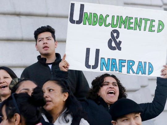 """FILE - In this Wednesday, Jan. 25, 2017 file photo, Lordes Reboyoso, right, yells at a rally outside of City Hall in San Francisco. President Donald Trump moved aggressively to tighten the nation's immigration controls Wednesday, signing executive actions to jumpstart construction of his promised U.S.-Mexico border wall and cut federal grants for immigrant-protecting """"sanctuary cities."""" On Tuesday, April 25, 2017, a federal judge blocked a Trump administration order to withhold funding from communities that limit cooperation with U.S. immigration authorities, saying the president has no authority to attach new conditions to federal spending."""