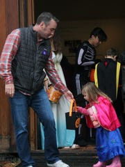 Charlee Sleeper, 3, of South Burlington, right, peeks into her basket of candy held by her father during Haunted Happenings at the Shelburne Museum on Sunday, Oct. 29, 2017.