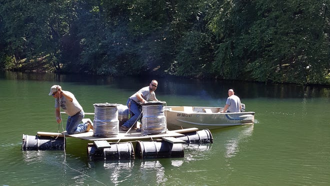Lancaster Parks Department employees installs weighted tubing from the shore to aerators Sept. 12 in Lake Loretta at Alley Park in Lancaster. The parks department was able to purchase an aerator system for Lake Loretta in an effort to bring the lake back to life.