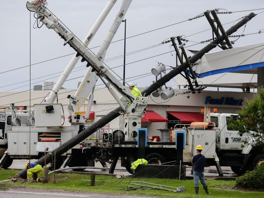 A utility crew works to repair a downed power pole caused by a possible tornado in Crowley as storms swept through Acadiana.