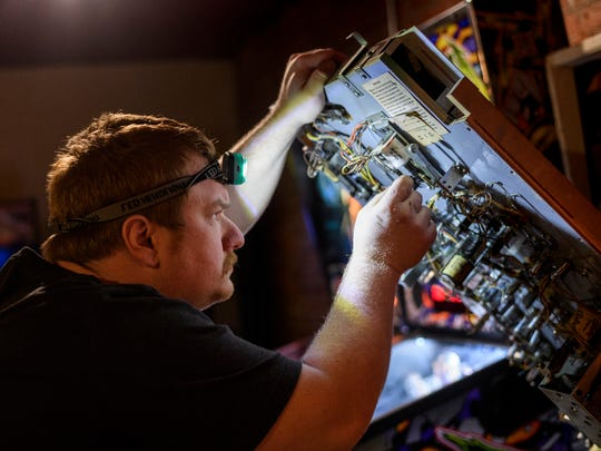 Jared Neible, co-owner of High Score Saloon, diligently works to repair a pinball machine, Thursday evening, March 29, 2018. The arcade currently has 12 pinball machines for patrons to play.