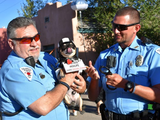 Bruiser, a dog entered in the Halloween on Granado Street's pet costume contest, gets his mugshot taken with two Tularosa police officers.