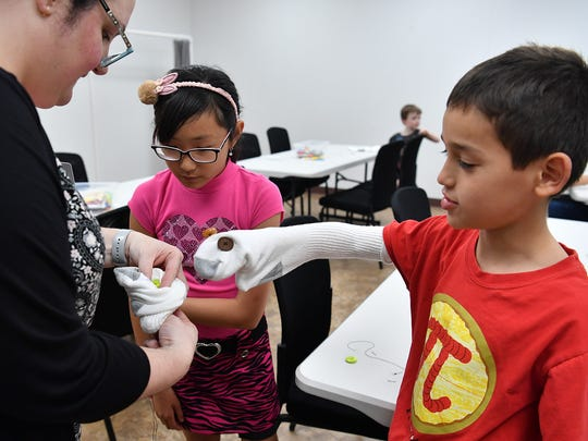 Celena Bradley shows Alice Chang how sew eyes on her sock puppet as Jude Zavala's sock puppet watches during Maker Monday at the Wichita Falls Public Library.