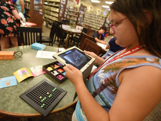 Marina Lopez (age 11), a volunteer, plays with Bloxels