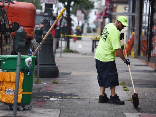 Paterson resident Jeremy Lisowski (age 41), Andres Scott (age 32), Evetta Thomas (age 55) clean the street near the corner of Main Street and Genessee Ave. in Paterson on 09/12/18. Paterson has given temporary, part-time jobs paying $14.42 to 17 people to clean the streets in about 29 different commercial strips.